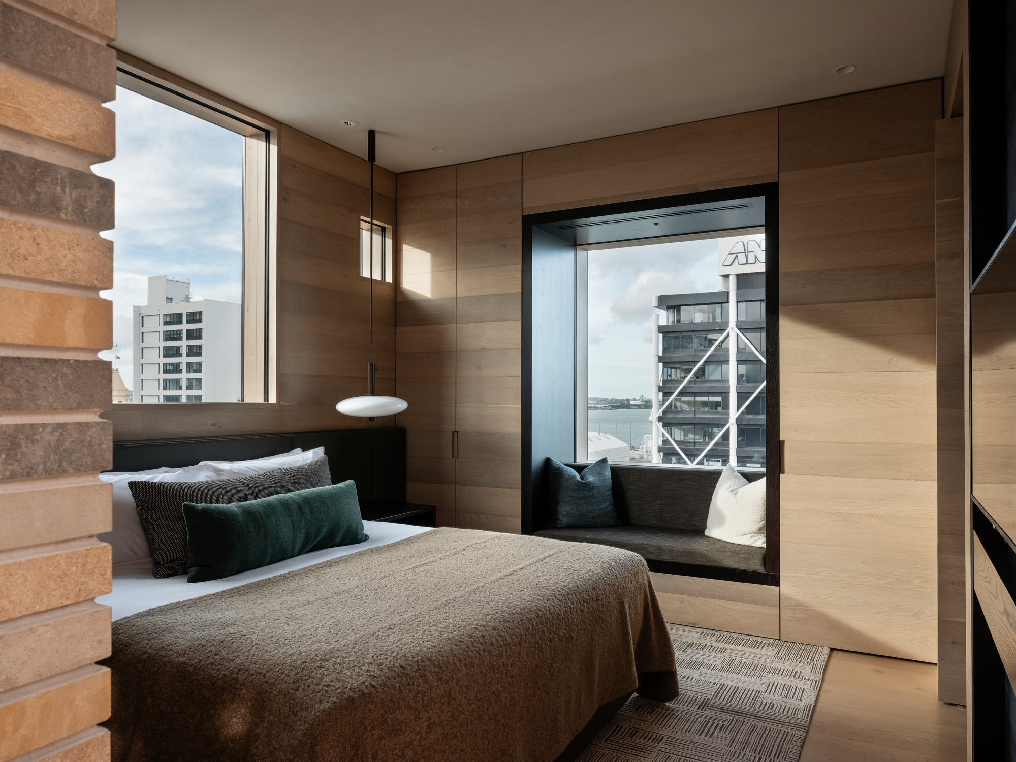 Wairoa suite bedroom with window seat facing out to city - The Landing Suites at The Hotel Britomart